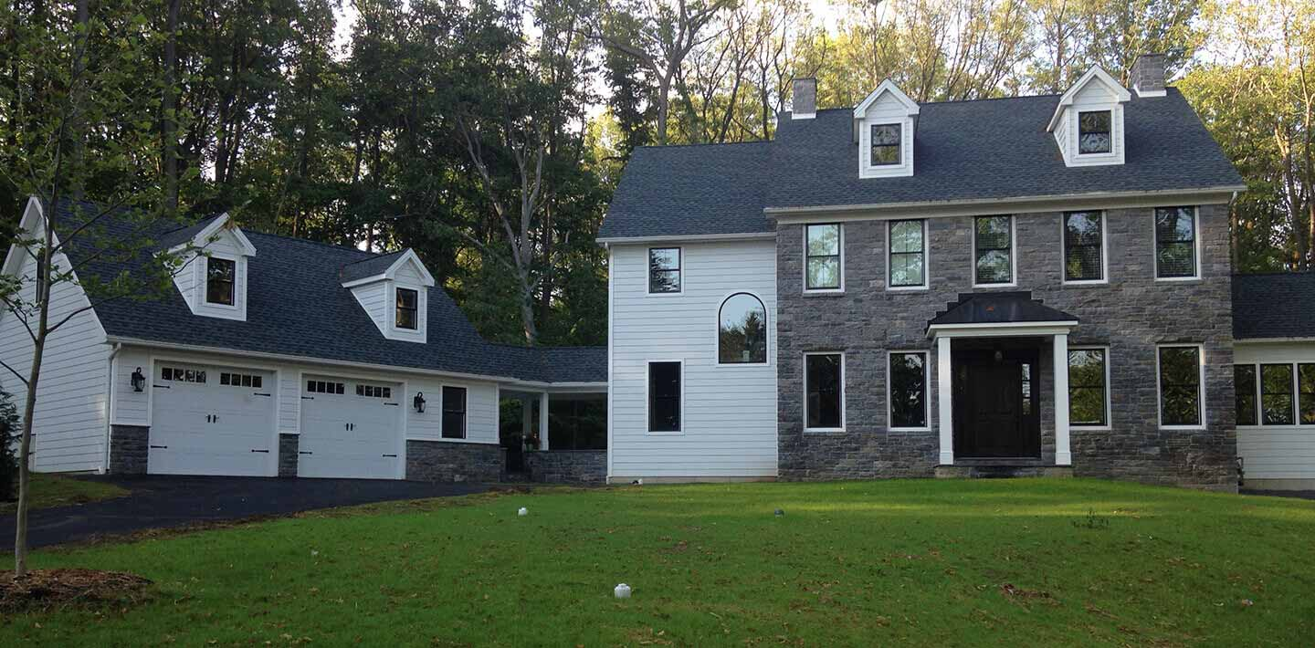 large stone and white vinyl cape cod home with attached vinyl cape cod garage